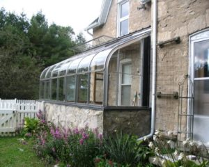 A curved-top greenhouse attached to a house